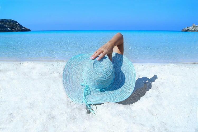 Rentière sur une plage grâce à son portefeuille de rentier